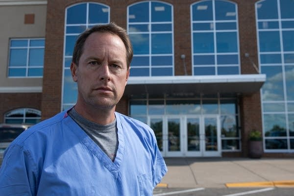 A man in scrubs in front of a building.