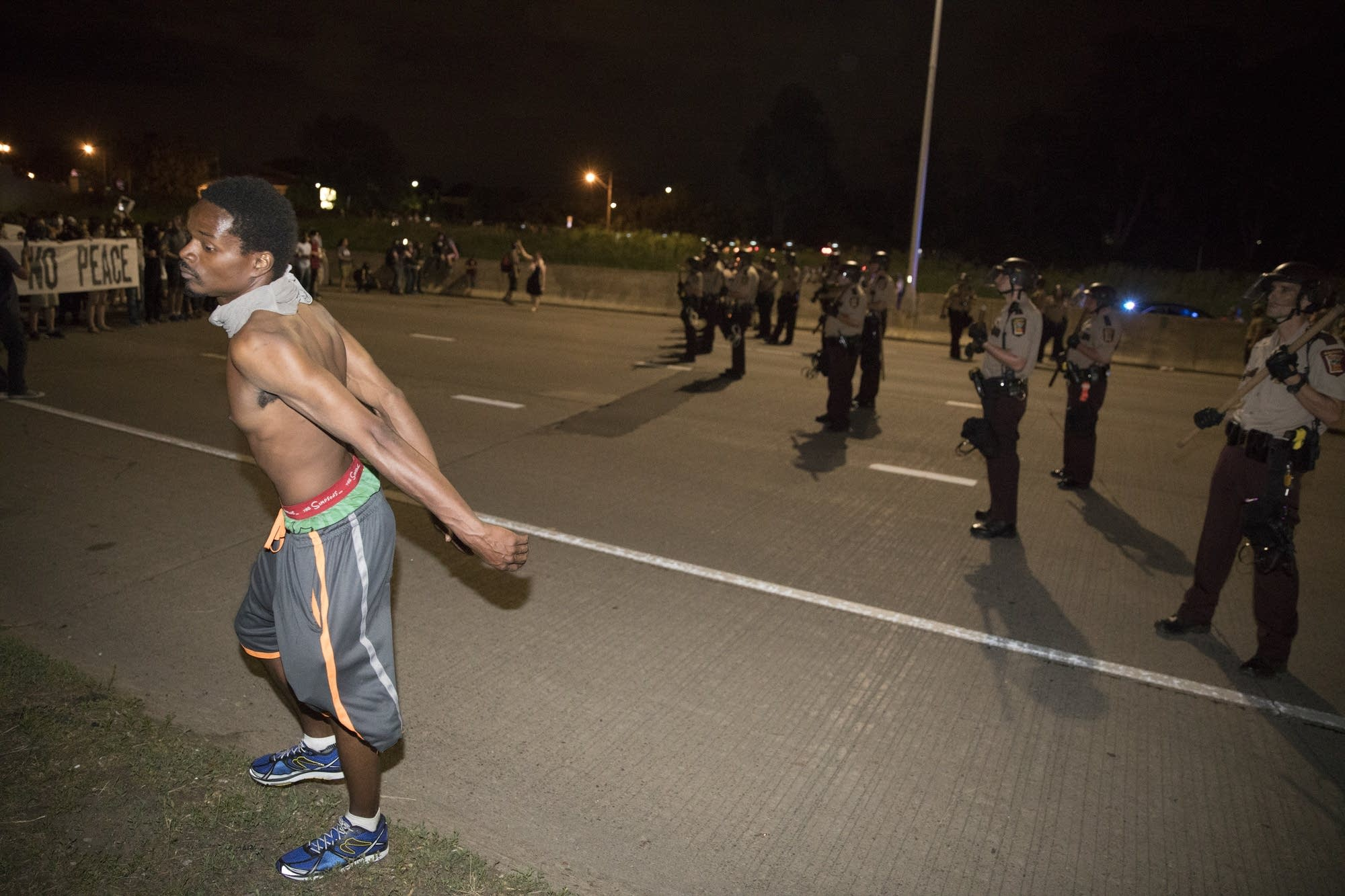 A protester stands with his hands behind his back, asking to be arrested.