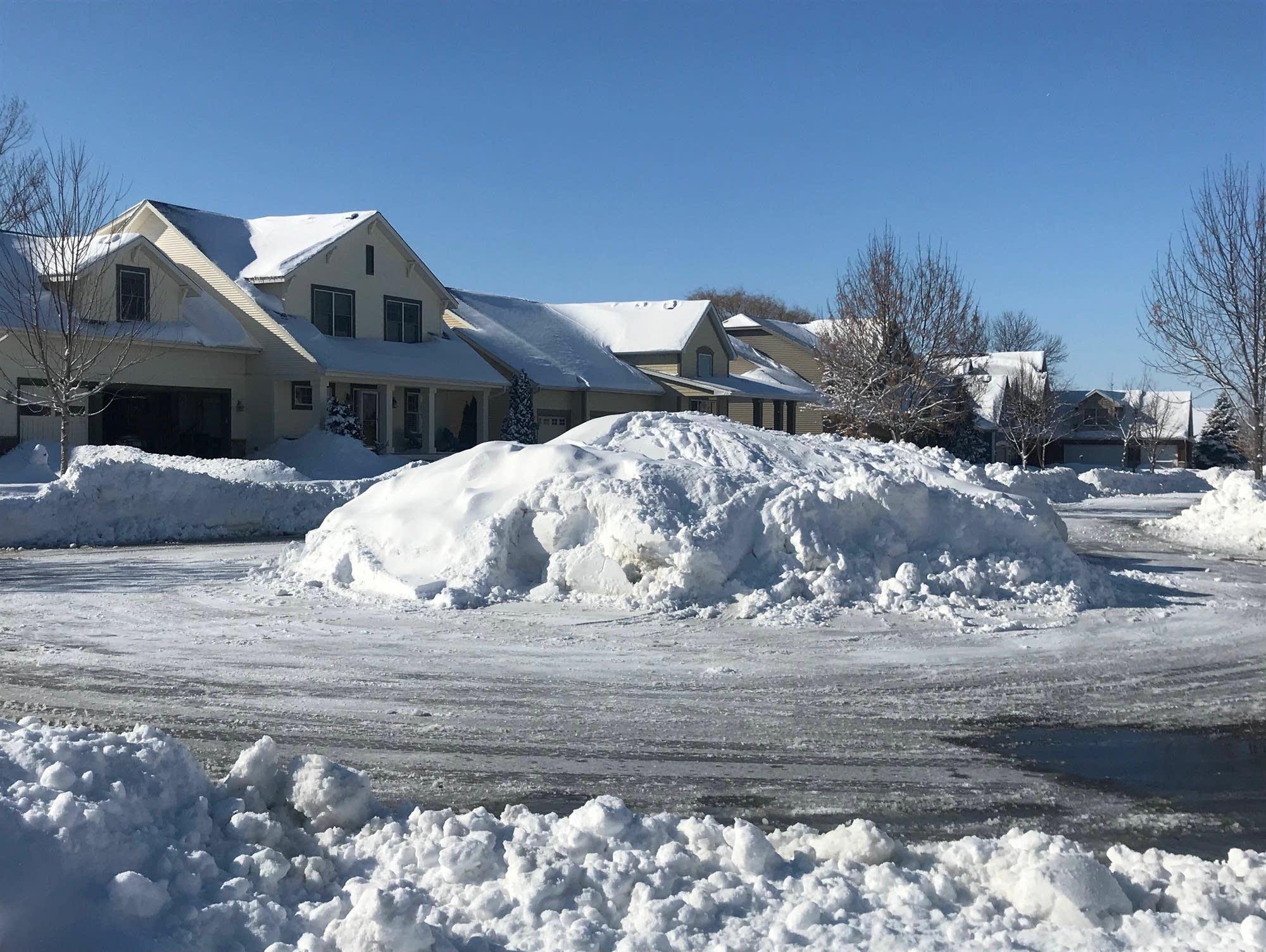 Massive piles of snow line a street in Chaska, Minn.