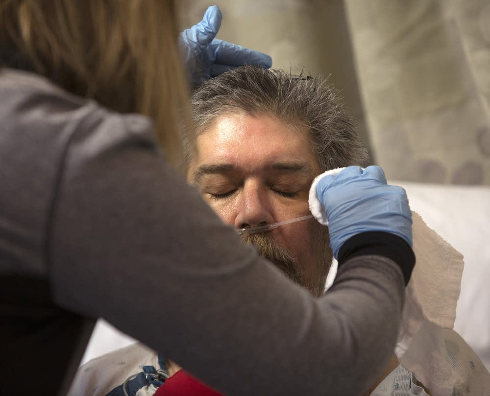 ICU patient Daniel Hage  has his face washed.