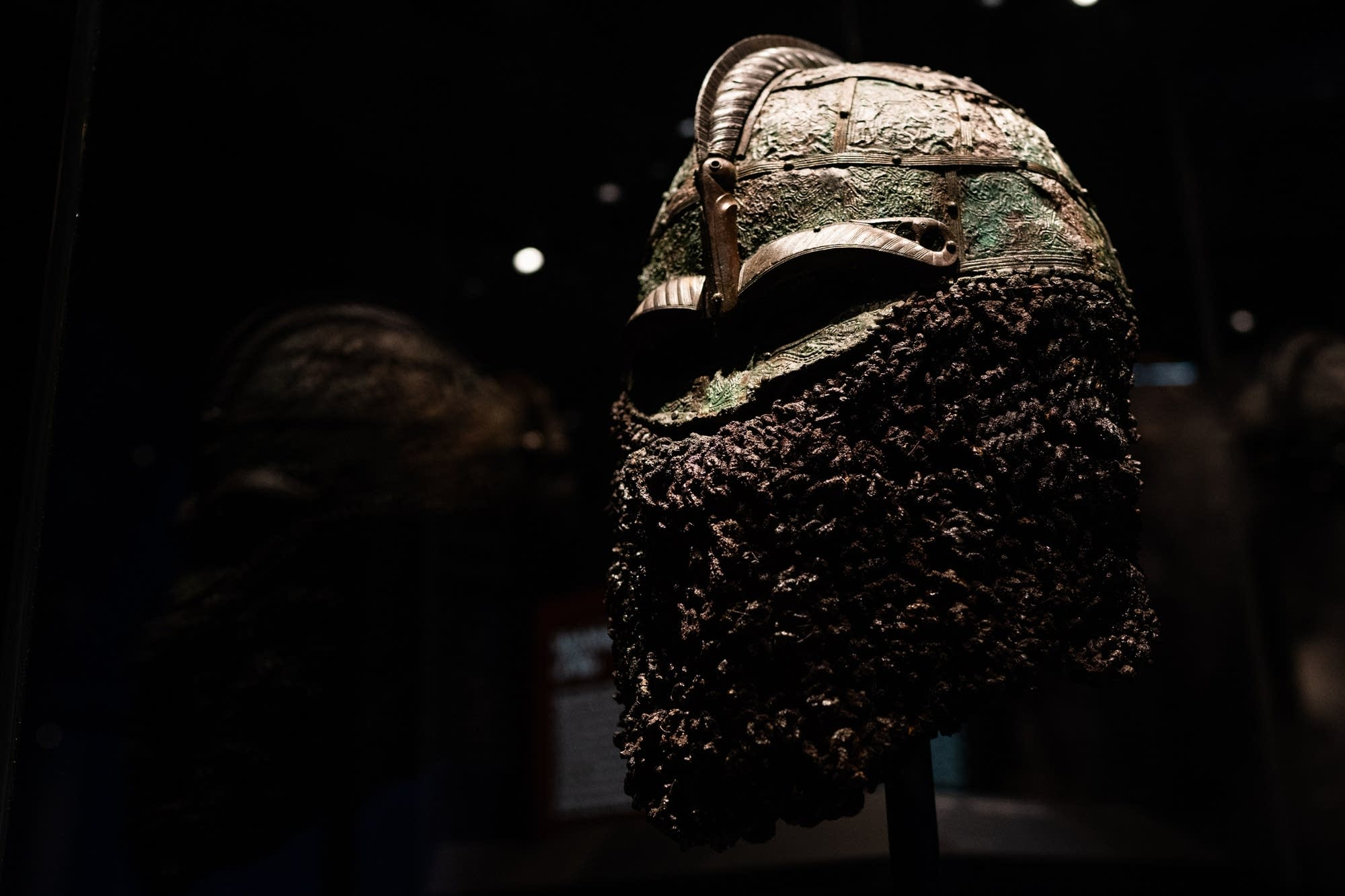 A Viking battle helmet with a face guard sits on display.