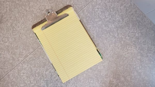 Photo of an old clipboard with a yellow legal pad clipped into it