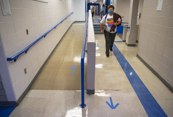 A students walks in a hall with taped arrows on the floor.