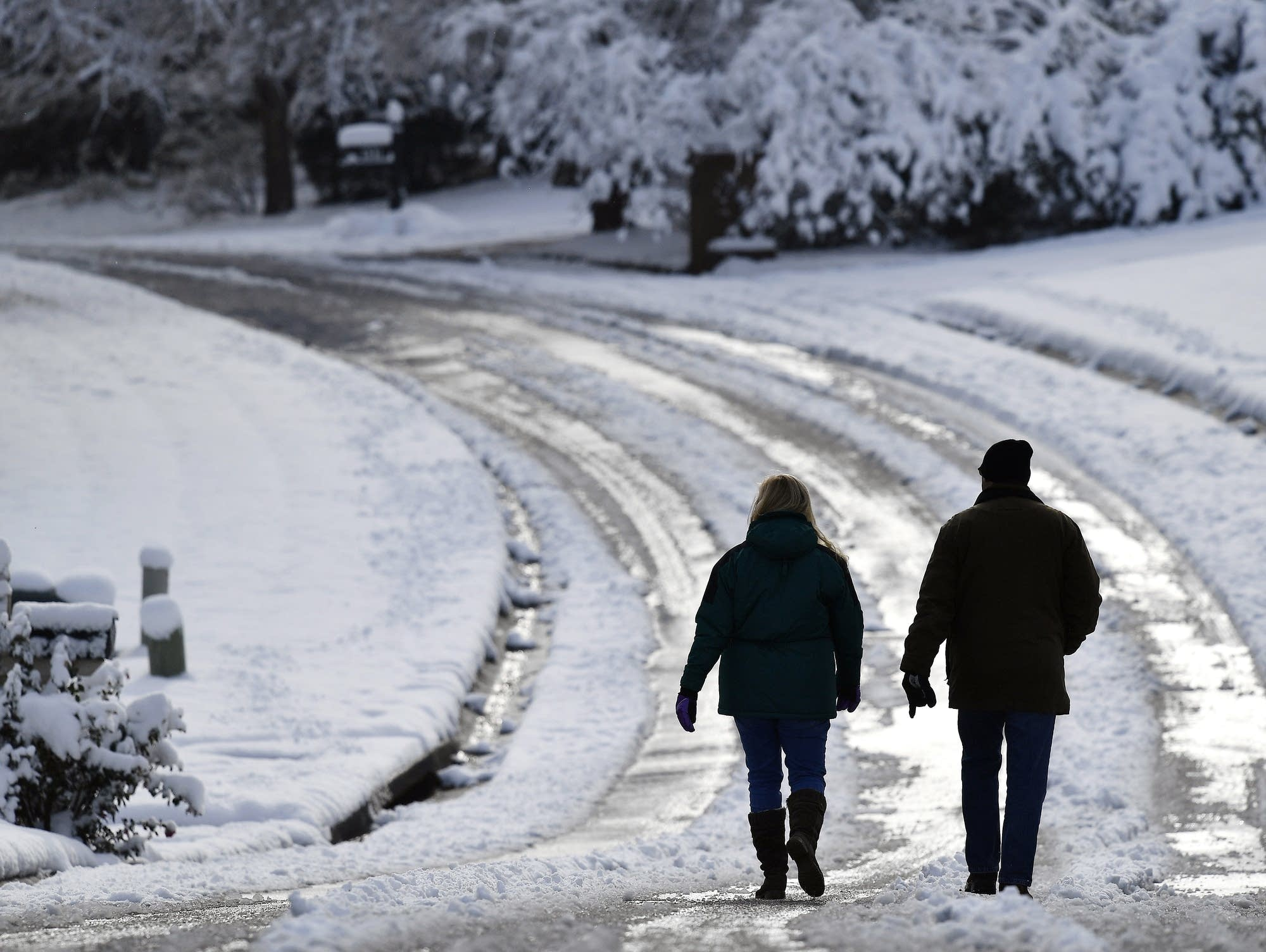 People walk down a snow covered road in Kennesaw, Ga.