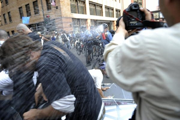 A protester gets hit by pepper spray