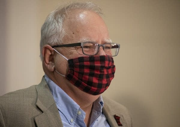 A man wearing glasses and a red and black plaid face mask.
