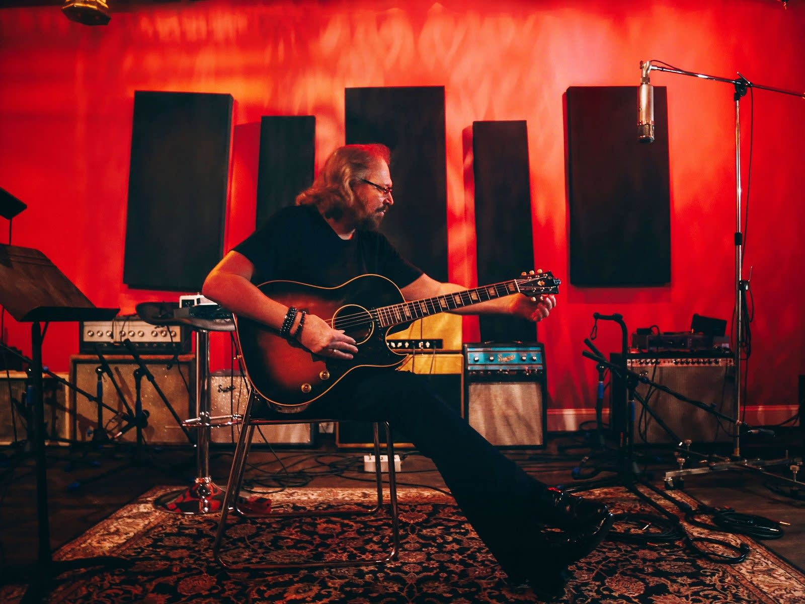 Barry Gibb tunes a guitar in a recording studio