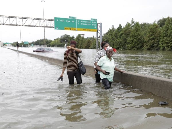 Evacuees wade down a flooded Interstate 610
