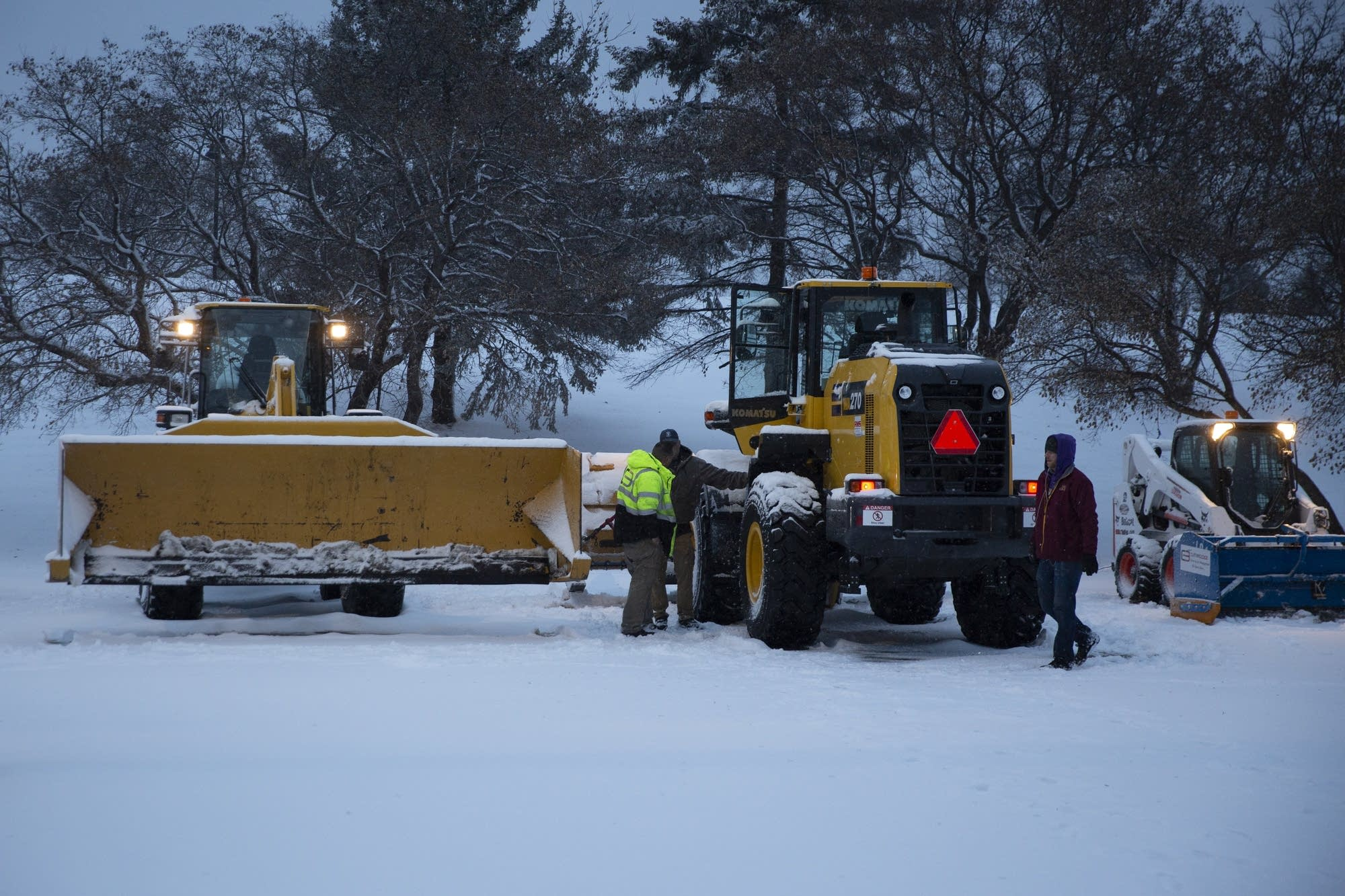 Crews prepare to plow and clear the parking lot.