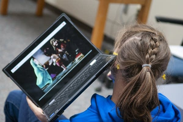 A teen holds up a laptop that's playing a movie to her ear.