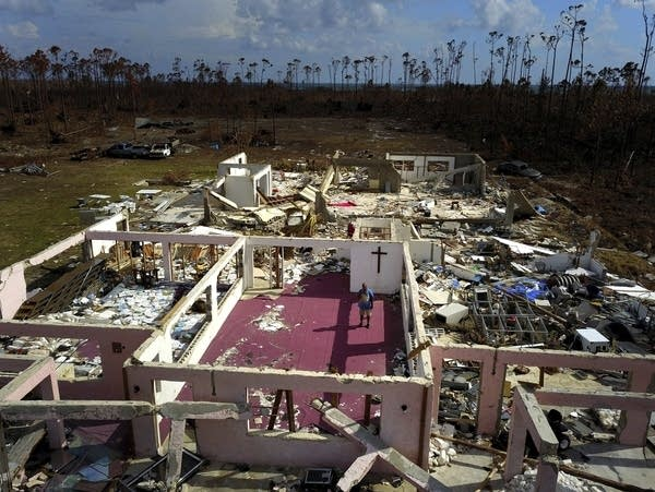 Pastor Jeremiah Saunders stands among the ruins of his church