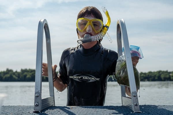 A young woman in a facemask and snorkel climbs a ladder onto a boat.