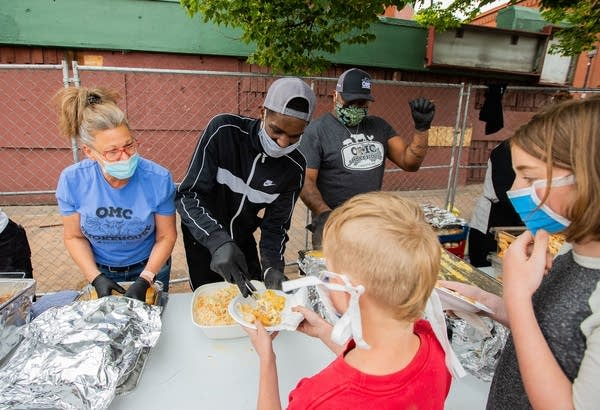 People serve food to kids.