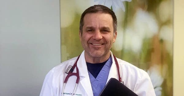 A man wearing a scrubs, a doctor's coat and stethoscope.