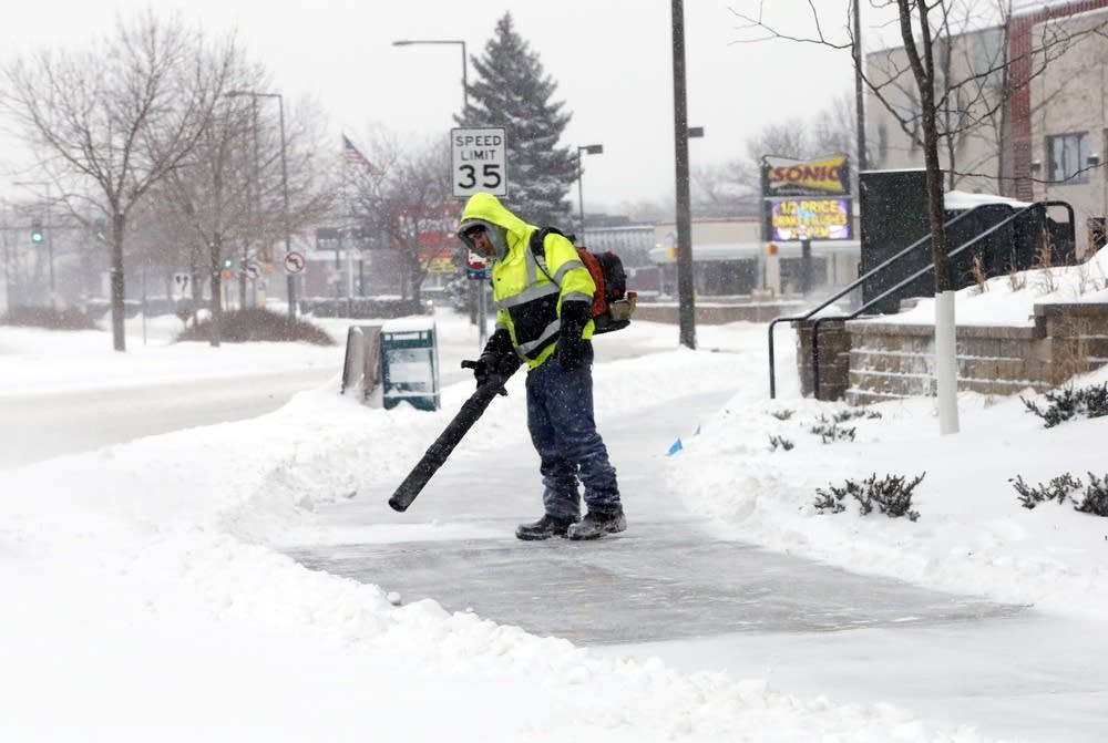 Clearing snow with a leaf blower.