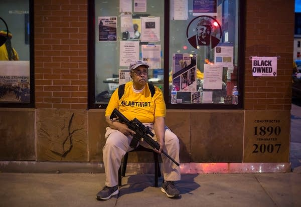 A man holds a gun as he sits on a chair outside a business.