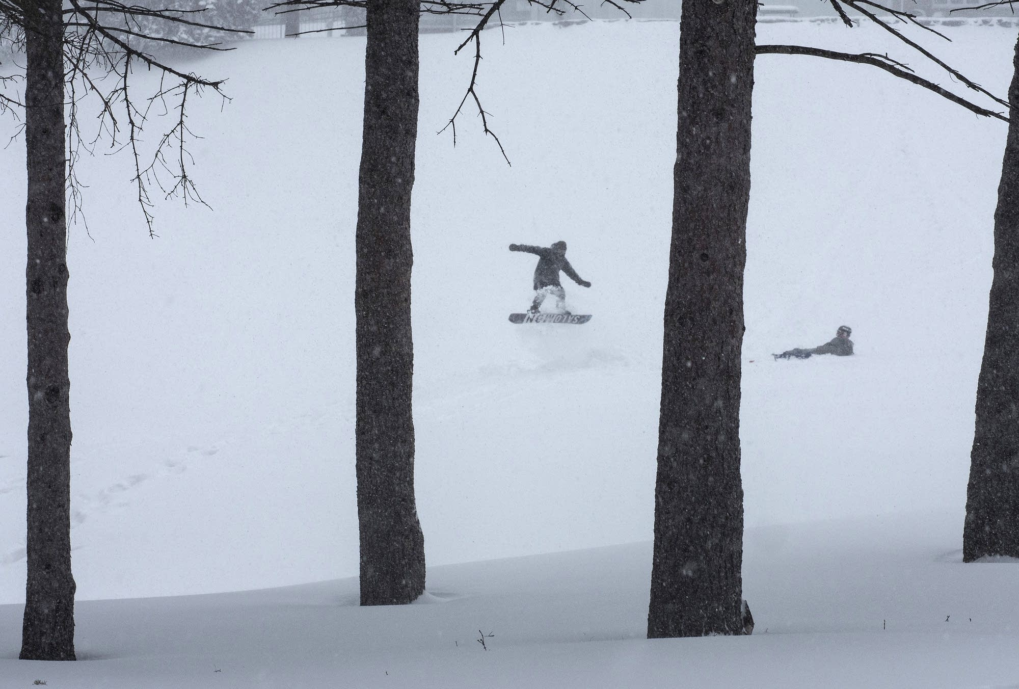 Two snowboarders were the only ones taking advantage of fresh powder.