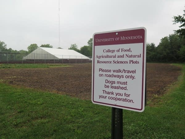 A sign in front of a field of dirt.