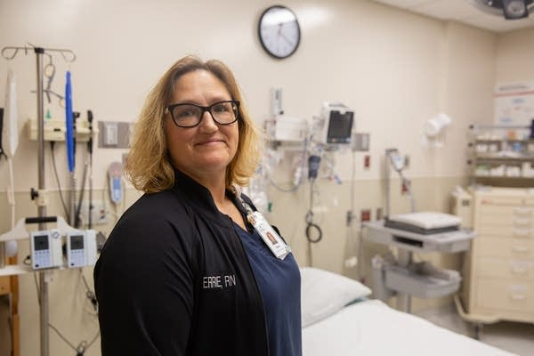 A woman stands in an emergency room