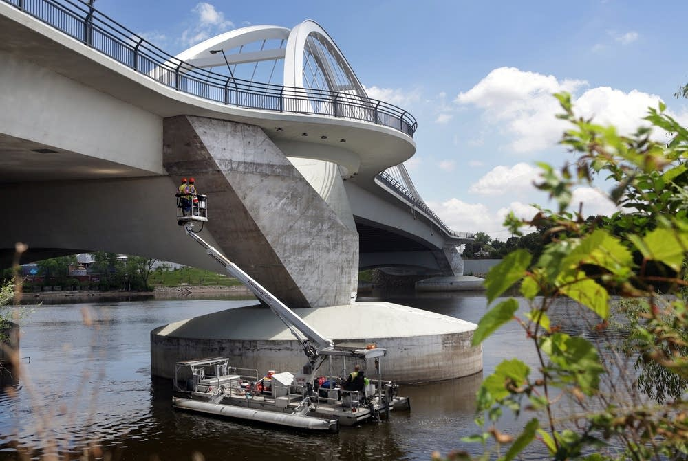 Hennepin County inspectors use a large pontoon boat with a boom lift.