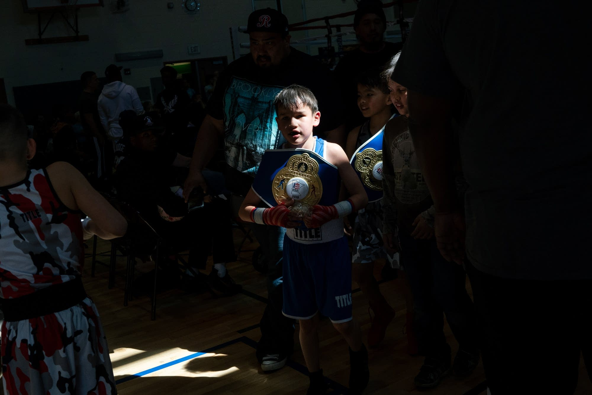 Nine-year-old Stanley Torres walks out of the gym with his belt.