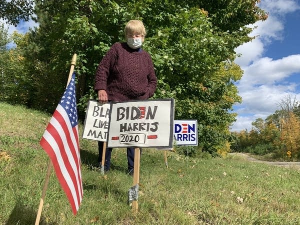 A woman wearing a mask fixes a hand-made yard sign.