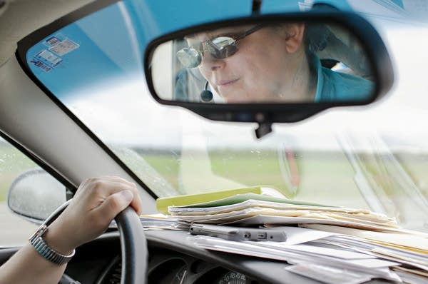 A woman's face is reflected in a rearview mirror of a car.