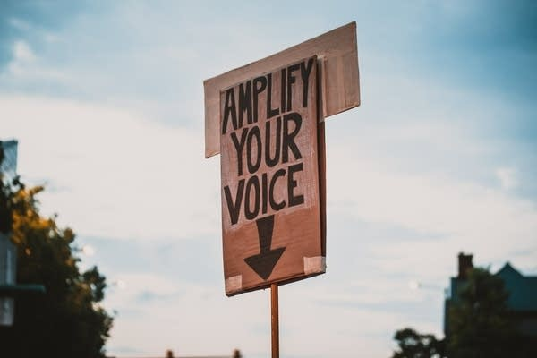 "A sign with the words ""amplify your voice"""