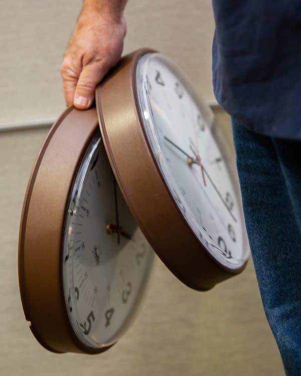 A hand holds 2 clocks.