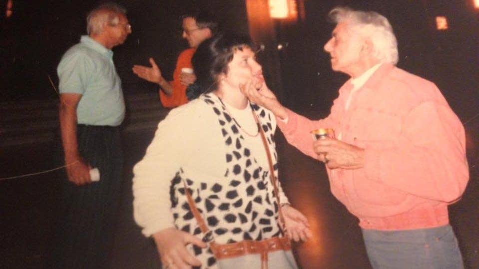 Leonard Bernstein grabs Angelina Reaux's cheeks.