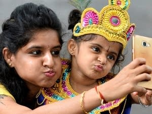 A mother takes a selfie with her child dressed as the Hindu deity Krishna