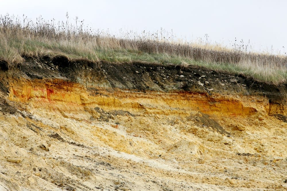 Side of a bluff shows layers of clay and sand.