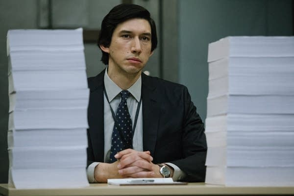 A man at a desk in between large stacks of paper.