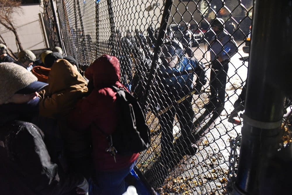 Police prod protesters away from the fence.