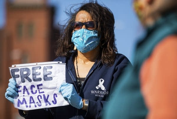 "Person wearing mask holds sign that reads ""free face masks"""