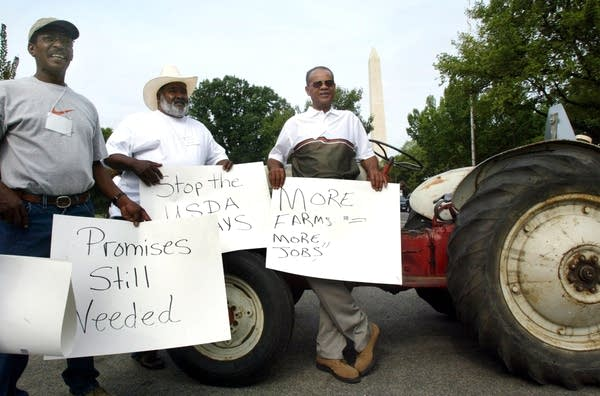 Three men stand with signs in front of a tractor.