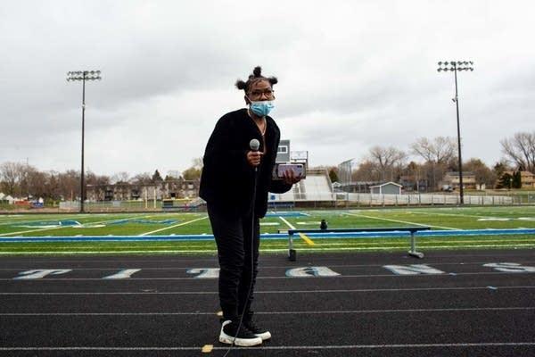 A student talks through a microphone on a football field.
