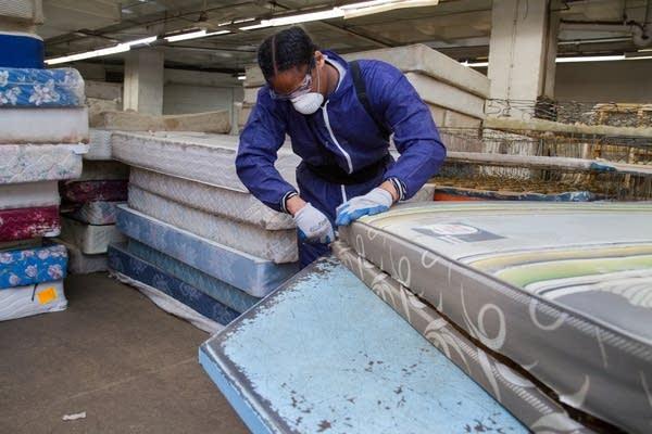 Mattress recycling worker takes apart a mattress.