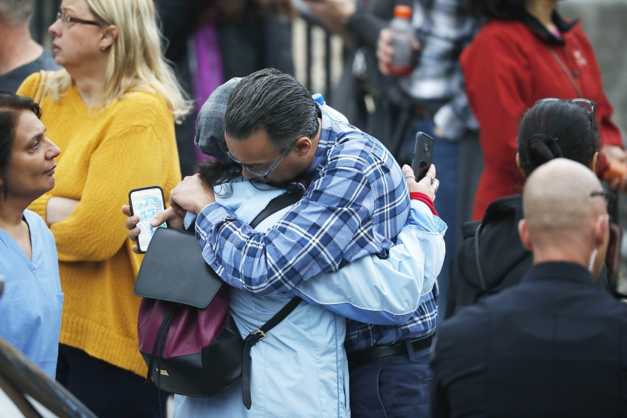 Parents hug as they wait for the arrival of their children.