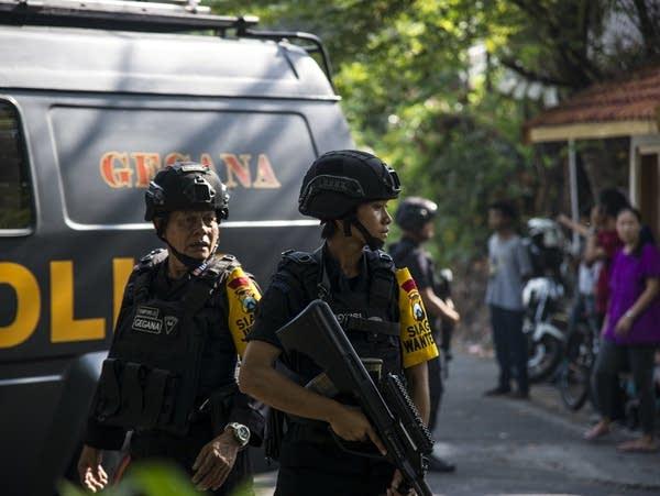 Indonesian policemen patrol outside a church