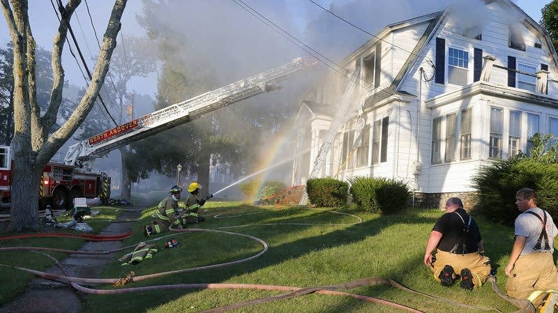 Firefighters battle a house fire in North Andover, Mass.