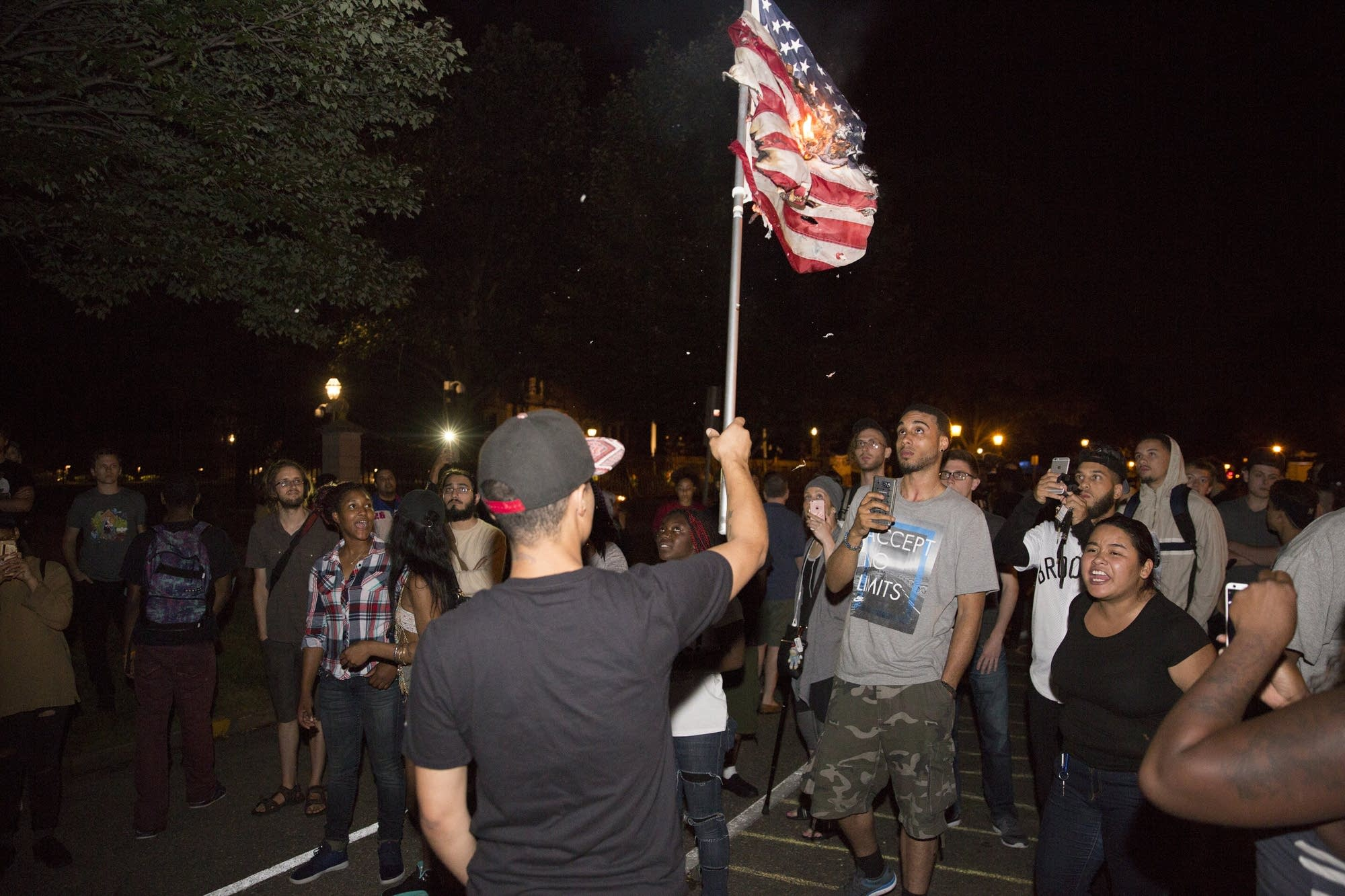 A protester held up a burning America flag.