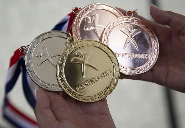 Four medals (a gold, silver and two bronze) are held in a woman's hands.