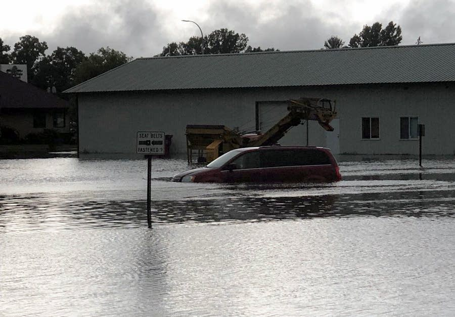 A car drives through a flooded road in Mora.