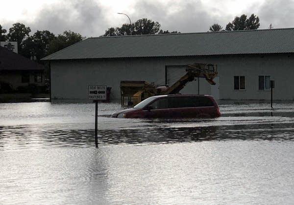 A car drives through a flooded road in Mora.