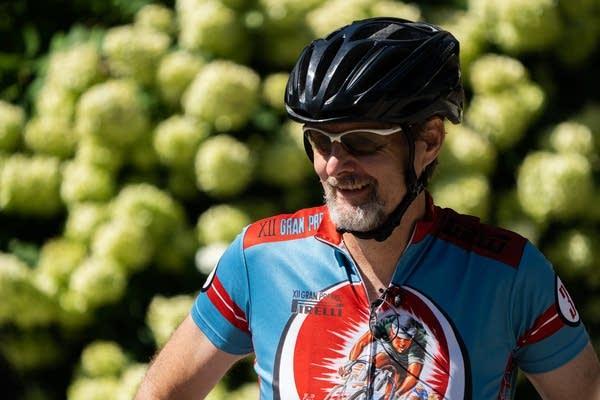 A man in a bike helmet smiles.