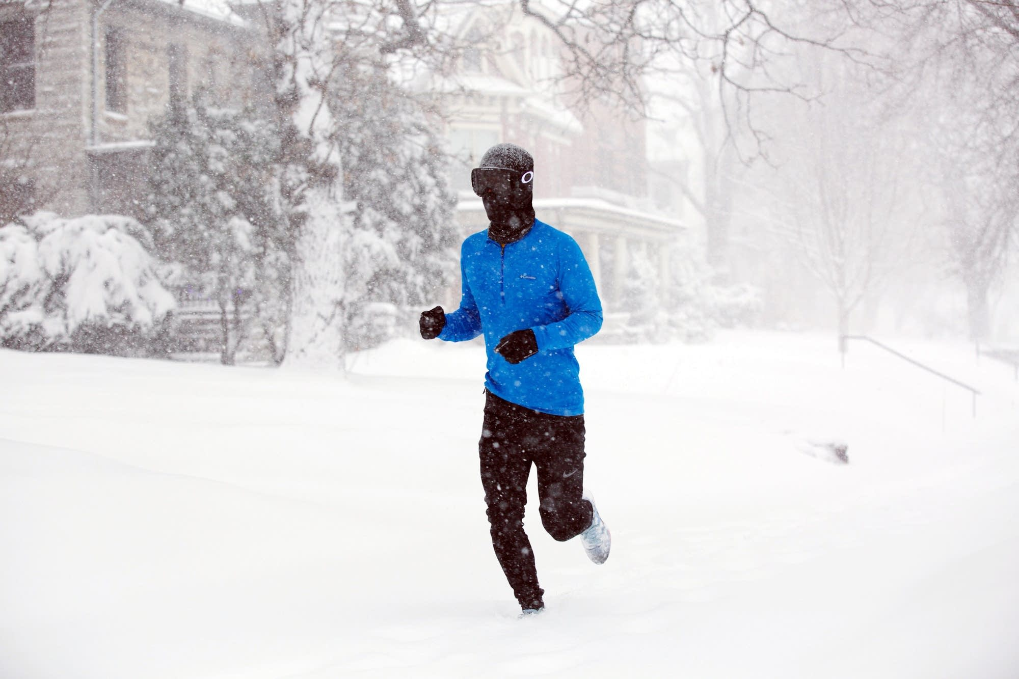 A man runs down Summit Ave. in St. Paul in the storm.