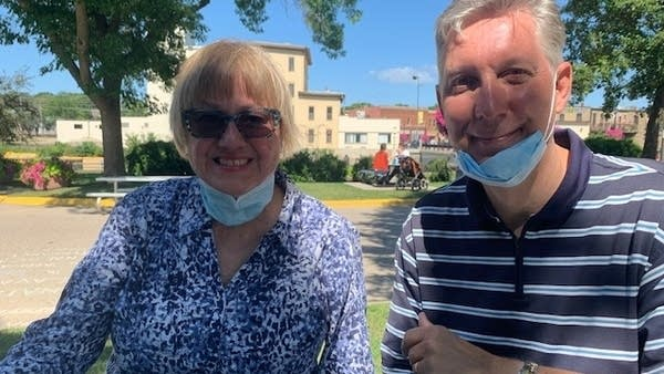 Two people sitting with masks