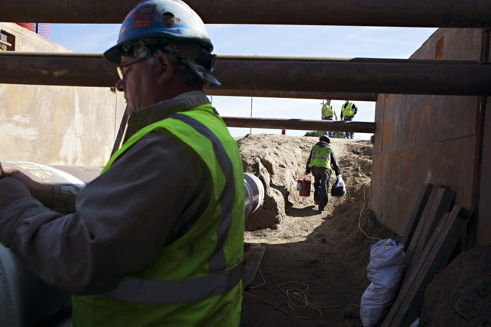 Workers repair and inspect an Enbridge pipeline