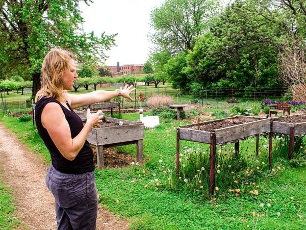A woman gestures out towards planting beds.